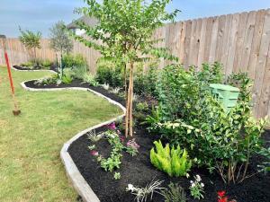 backyard landscape design flower bed mulching stone edging houston tx 77407